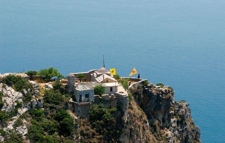 Στην άκρη του βράχου ένας μοναχός ανεμίζει μια μεγάλη κίτρινη σημαία με τον δικέφαλο αετό.