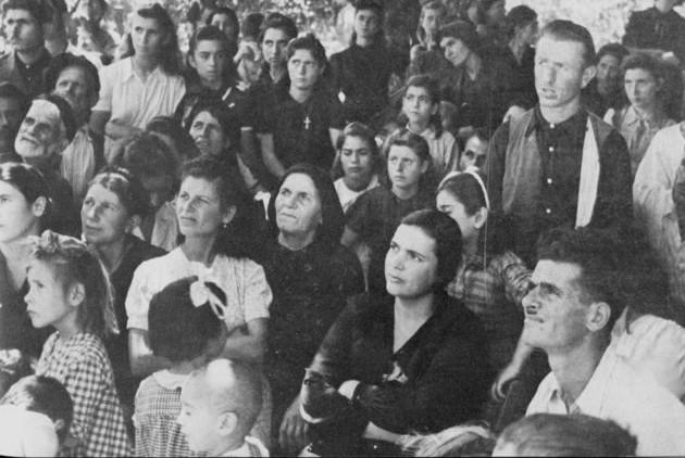 Φωτογραφία της ναζιστικής προπαγάνδας (22/7/1944) με λεζάντα: «Η Κρήτη μένει πιστή στην Ελληνική Υπόθεση. Με έντονο ενδιαφέρον ακούνε οι κάτοικοι του χωριού τις αφηγήσεις των Γερμανών από τις εμπειρίες τους με τον Μπολσεβικισμό»