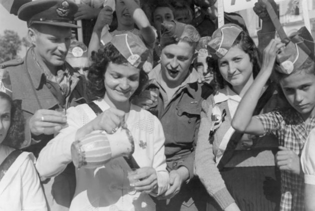 Κοπέλες της ΕΠΟΝ καλωσορίζουν τον βρετανικό στρατό σε προάστιο της Πάτρας (Οκτώβριος 1944)